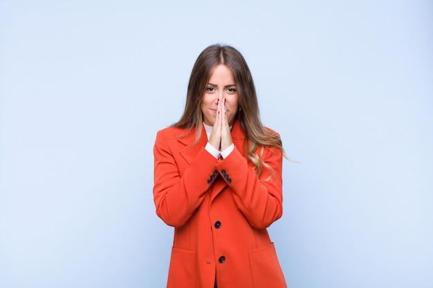 Joven mujer hispana bonita que se siente preocupada, esperanzada y religiosa, rezando fielmente con las palmas presionadas, pidiendo perdón contra la pared azul