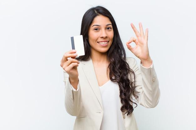 Joven mujer hispana bonita con una tarjeta de crédito
