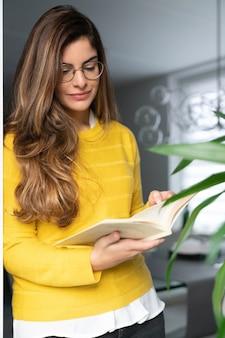 Joven mujer hispana en una camisa amarilla de pie junto a la ventana y leyendo un libro