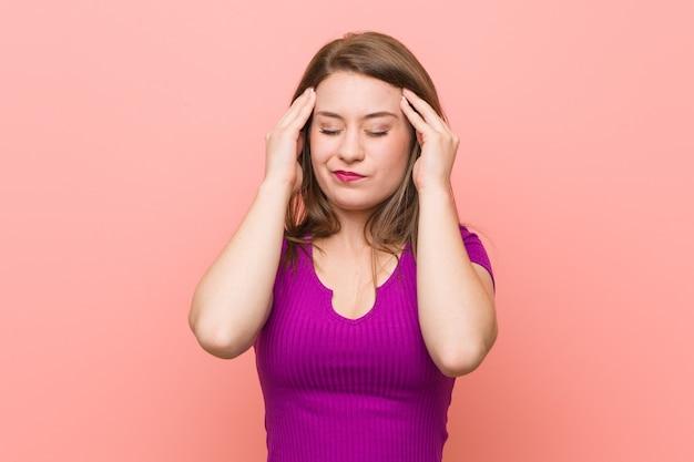 Joven mujer hispana contra una pared rosa tocar templos y tener dolor de cabeza.