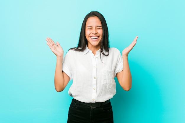 Joven mujer hispana fresca contra una pared azul alegre riendo mucho. concepto de felicidad