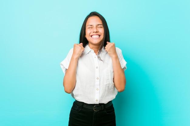 Joven mujer hispana fresca contra una pared azul levantando el puño, sintiéndose feliz y exitosa