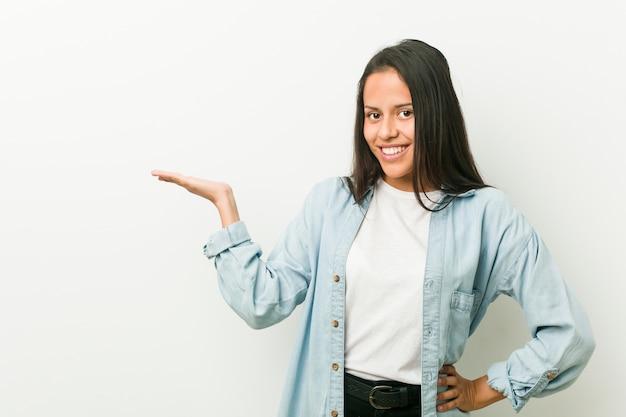 Joven mujer hispana mostrando una copia en una palma y sosteniendo otra mano en la cintura.