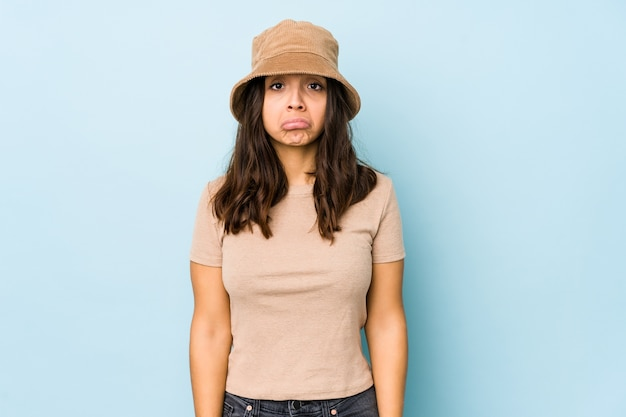 Joven mujer hispana de raza mixta aislada sopla mejillas, tiene expresión cansada. concepto de expresión facial.