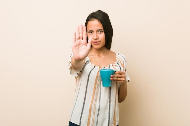 Joven mujer hispana sosteniendo una taza de pie con la mano extendida que muestra la señal de stop, impidiéndole.