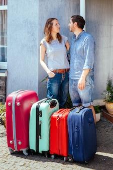 Joven mujer y hombre con mucha maleta cerca de casa lista para viajar