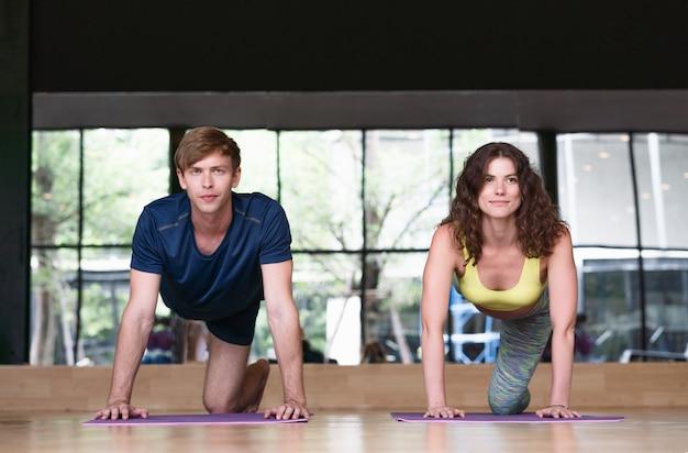 Joven mujer y hombre practica ejercicios de yoga interior en fitness