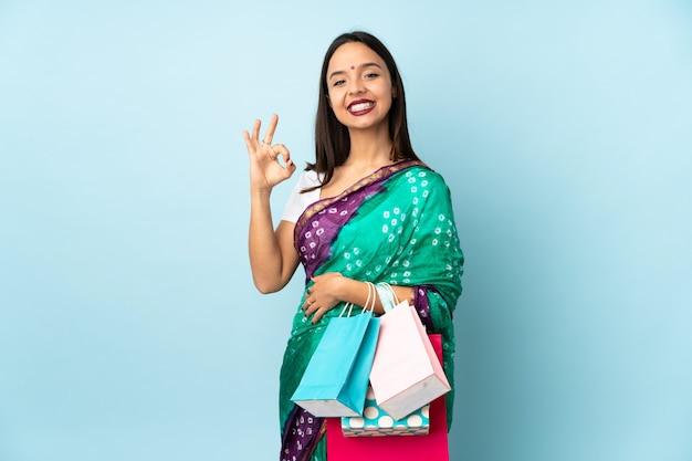 Joven mujer india con bolsas de la compra que muestra bien firmar con los dedos