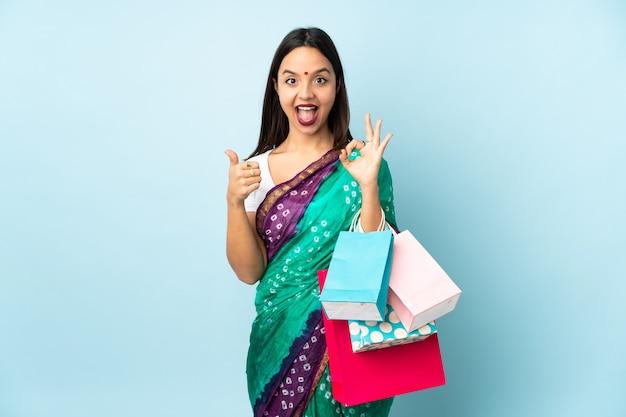 Joven mujer india con bolsas de la compra que muestra signo bien y pulgar arriba gesto