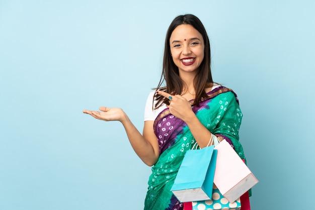 Joven mujer india con bolsas de compras con copyspace imaginario en la palma para insertar un anuncio