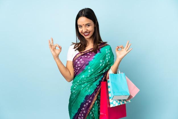 Joven mujer india con bolsas de compras en pose zen