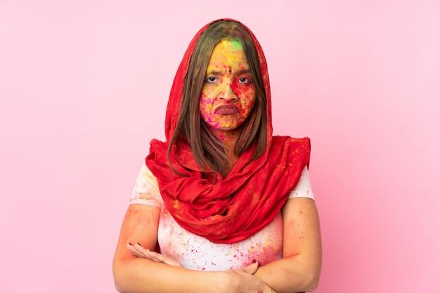 Joven mujer india con coloridos polvos de holi en la cara en la pared rosa sintiéndose molesta