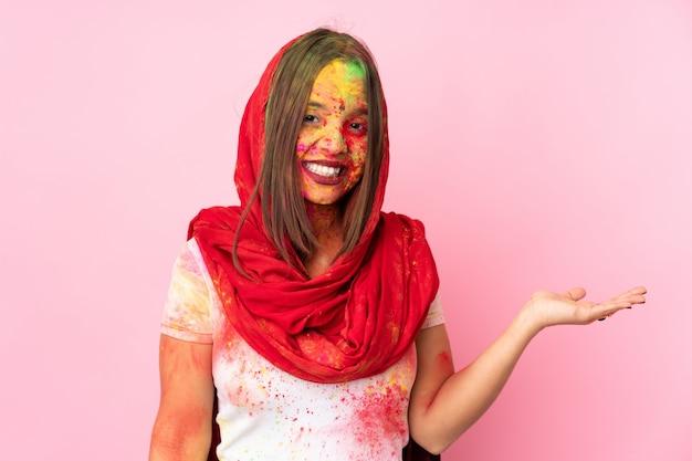 Joven mujer india con coloridos polvos de holi en su rostro aislado en la pared de color rosa con copyspace imaginario en la palma para insertar un anuncio