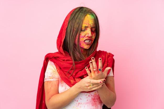Joven mujer india con coloridos polvos de holi en su rostro aislado en la pared rosa que sufre de dolor en las manos