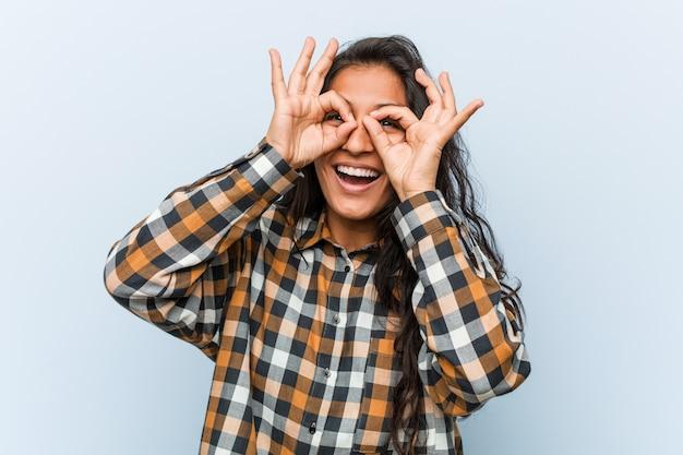 Joven mujer india fresca mostrando signo bien sobre los ojos