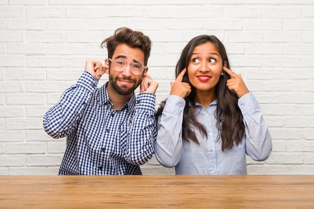 Joven mujer india y hombre caucásico pareja cubriendo orejas con las manos