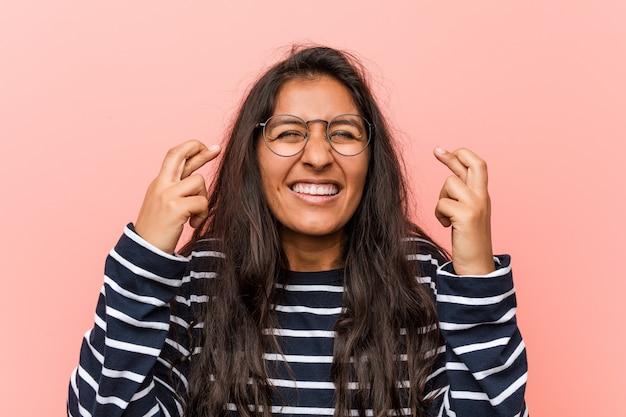 Joven mujer india intelectual cruzando los dedos para tener suerte