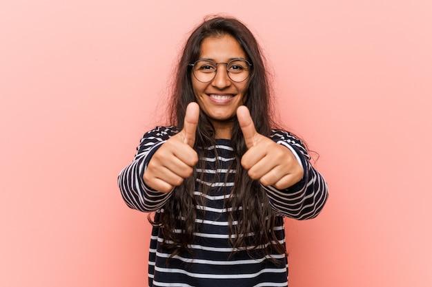 Joven mujer india intelectual con pulgares arriba, aplausos sobre algo, apoyo y respeto concepto.