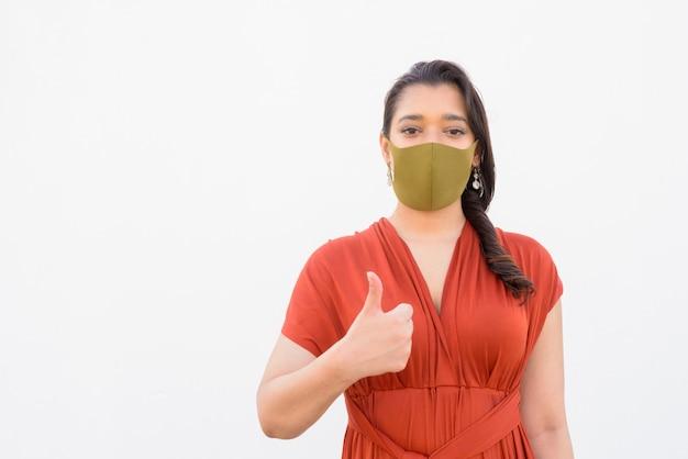 Joven mujer india con máscara dando pulgares contra el fondo blanco.