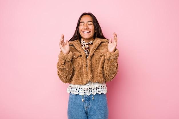 Joven mujer india de raza mixta con un abrigo corto de piel de oveja alegre riendo mucho