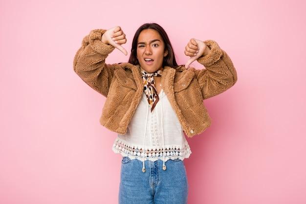 Joven mujer india de raza mixta con un abrigo corto de piel de oveja mostrando el pulgar hacia abajo y expresando disgusto.