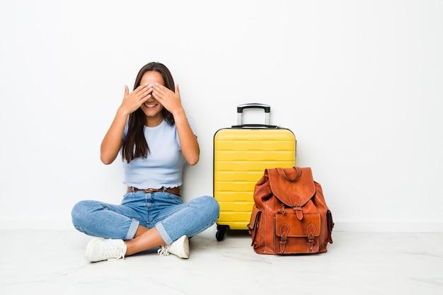 Joven mujer india de raza mixta lista para ir a viajar cubre los ojos con las manos, sonríe ampliamente esperando una sorpresa.