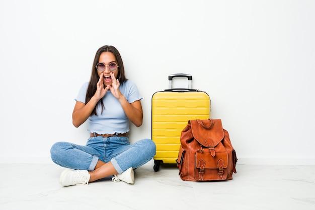 Joven mujer india de raza mixta lista para ir a viajar gritando emocionado al frente.