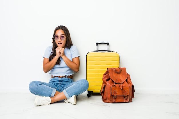 Joven mujer india de raza mixta lista para ir a viajar rezando por suerte, sorprendida y abriendo la boca mirando al frente.