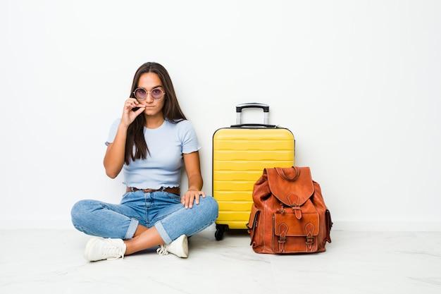 Joven mujer india de raza mixta lista para viajar con los dedos en los labios manteniendo un secreto.