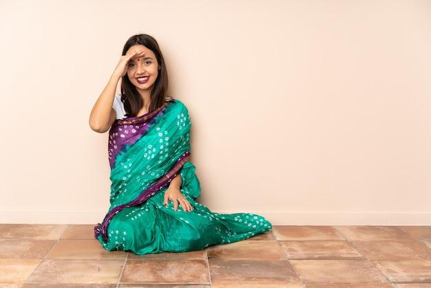 Joven mujer india sentada en el suelo saludando con la mano con expresión feliz