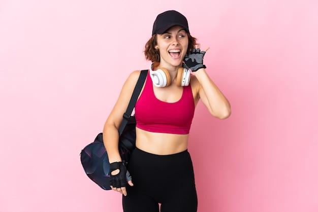 Joven mujer inglesa aislada en la pared rosa escuchando algo poniendo la mano en la oreja