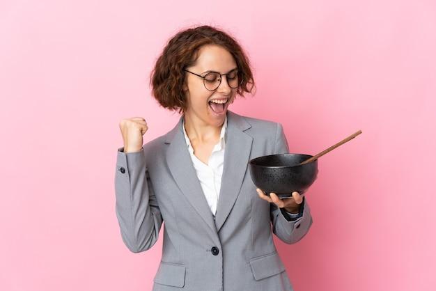 Joven mujer inglesa en rosa celebrando una victoria mientras sostiene un plato de fideos con palillos