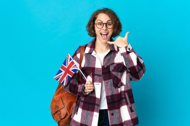 Joven mujer inglesa sosteniendo una bandera de reino unido aislada en la pared azul haciendo gesto de teléfono. llámame señal