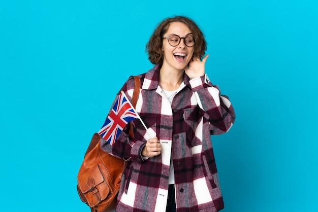 Joven mujer inglesa sosteniendo una bandera del reino unido en azul escuchando algo poniendo la mano en la oreja