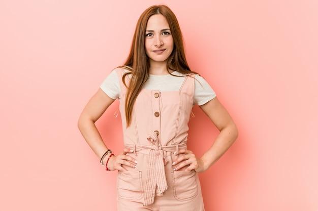 Joven mujer de jengibre con pecas confía en mantener las manos en las caderas