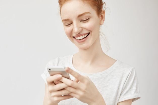 Joven mujer de jengibre sonriendo, enviando mensajes de texto publicando fotos en las redes sociales con una sonrisa