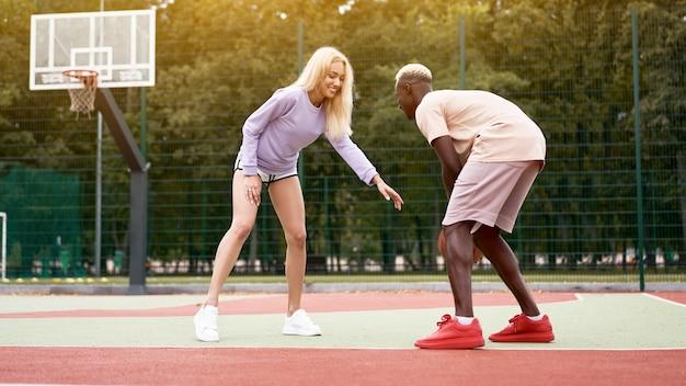 Joven y mujer jugando baloncesto al aire libre