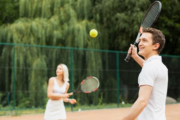 Joven y mujer jugando tenis