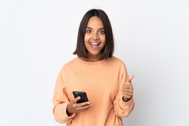 Joven mujer latina aislada en la pared blanca con teléfono móvil mientras hace los pulgares para arriba