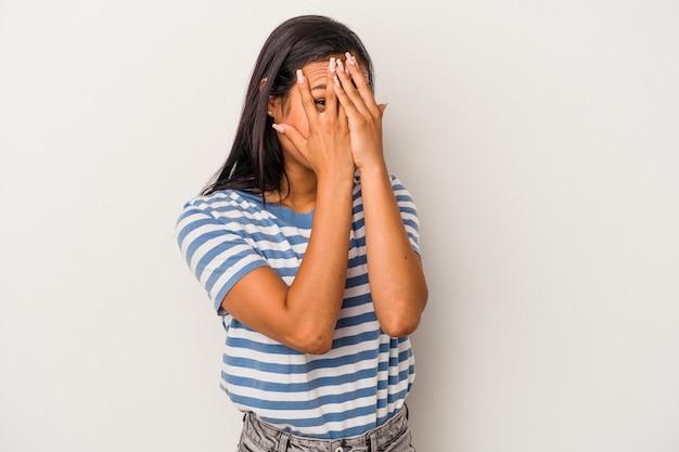 Joven mujer latina aislada sobre fondo blanco parpadea a través de los dedos asustada y nerviosa.