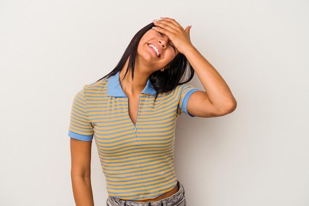 Joven mujer latina aislada sobre fondo blanco se ríe con alegría manteniendo las manos en la cabeza. concepto de felicidad.
