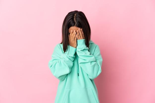 Joven mujer latina aislada sobre fondo rosa con expresión cansada y enferma