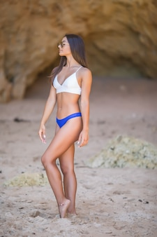 Joven mujer latina en bikini caminando cerca de las rocas mirando al mar durante las vacaciones de verano