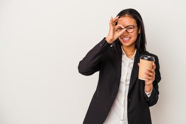 Joven mujer latina de negocios sosteniendo un café para llevar aislado sobre fondo blanco emocionado manteniendo el gesto ok en el ojo.