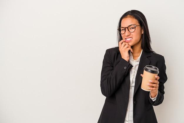 Joven mujer latina de negocios sosteniendo un café para llevar aislado sobre fondo blanco mordiéndose las uñas, nerviosa y muy ansiosa.