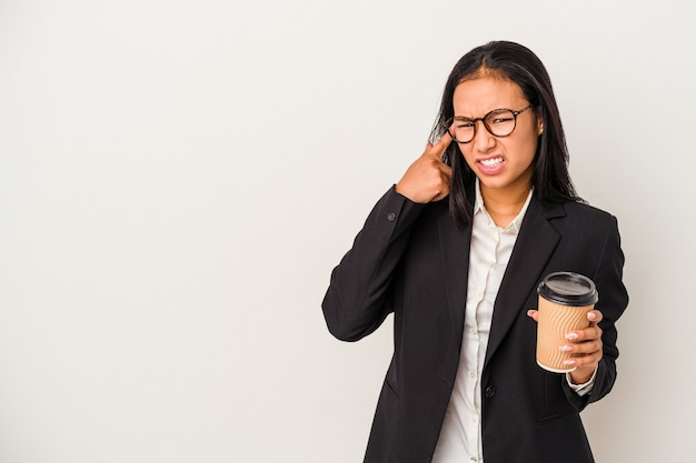 Joven mujer latina de negocios sosteniendo un café para llevar aislado sobre fondo blanco mostrando un gesto de decepción con el dedo índice.