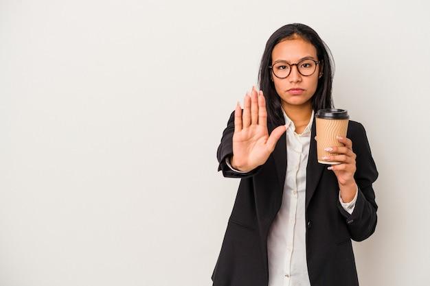 Joven mujer latina de negocios sosteniendo un café para llevar aislado sobre fondo blanco de pie con la mano extendida mostrando la señal de stop, impidiéndote.