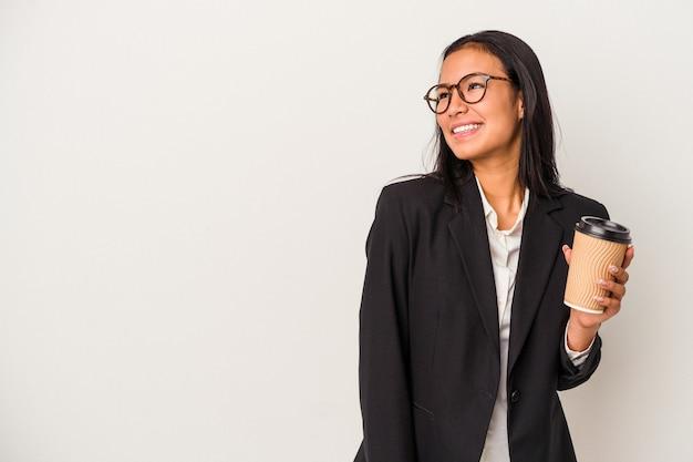 Joven mujer latina de negocios sosteniendo un café para llevar aislado sobre fondo blanco se ve a un lado sonriente, alegre y agradable.