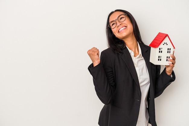 Joven mujer latina de negocios sosteniendo una casa de juguete aislada sobre fondo blanco apunta con el dedo pulgar lejos, riendo y sin preocupaciones.