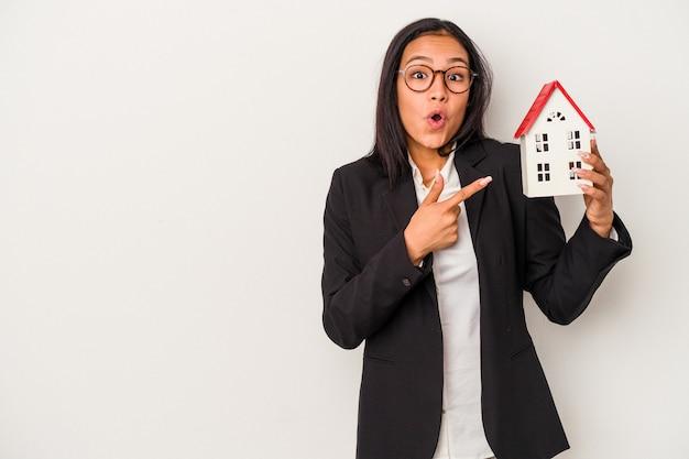 Joven mujer latina de negocios sosteniendo una casa de juguete aislada sobre fondo blanco apuntando hacia el lado